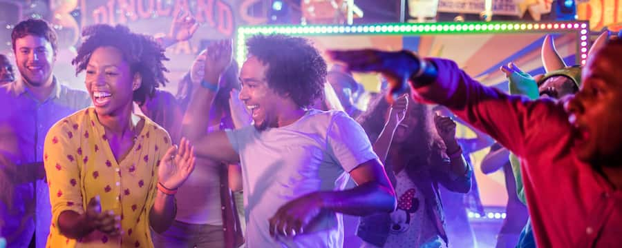 2 young adults dancing together at an outdoor Dance Party at Dinoland