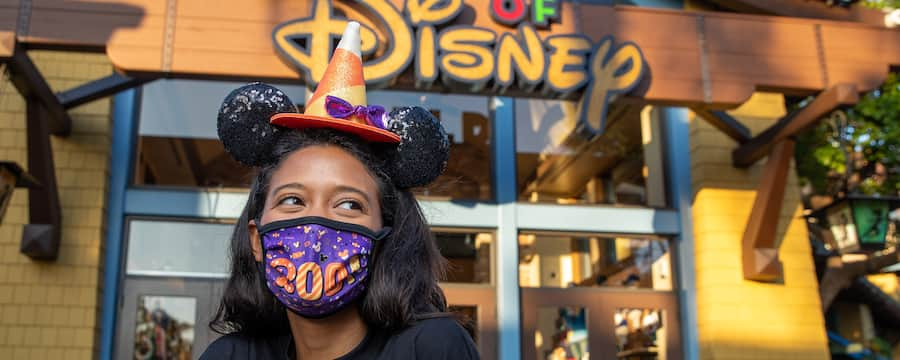 A young woman wearing a Minnie Mouse Halloween earband by a storefront with a sign that reads 'World of Disney'