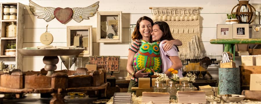 Mom and daughter hugging in a store that offers rustic, artisan-style merchandise