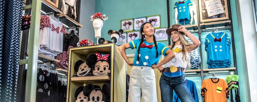 2 jóvenes Visitantes lucen prendas de Disney en una tienda