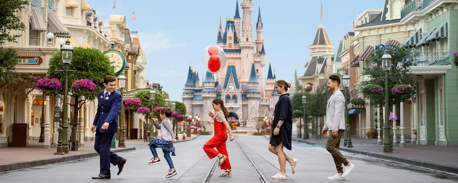 A family follows a Tour Guide in a line on Main Street, USA