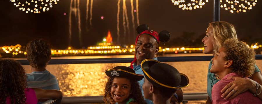 A father, daughter and son in pirate hats smile at each other while watching a firework display
