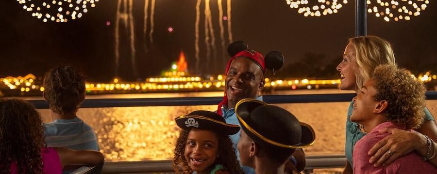 Un padre, su hija y su hijo con sombreros de pirata comparten sonrisas durante un espectáculo de fuegos artificiales