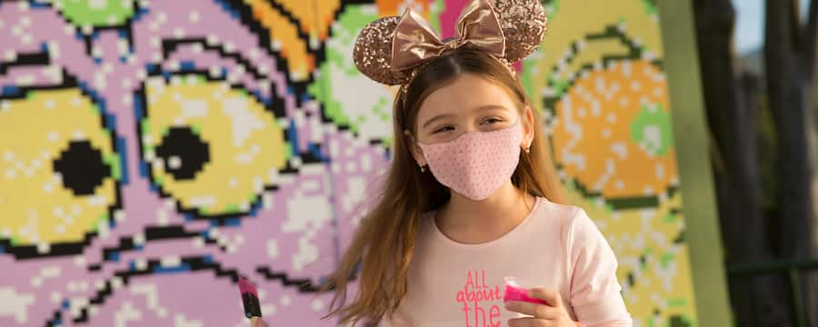 A girl with face mask wearing Minnie Mouse ears holds a small container of paint and a brush