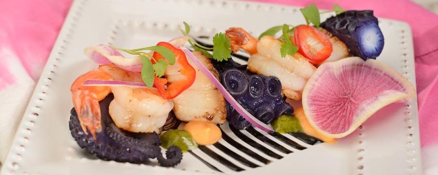 Cóctel de mariscos fríos, con pulpo, vieiras, camarones, alioli de ajo negro, salsa de tomate y coco y aceite de chile serrano y limón verde