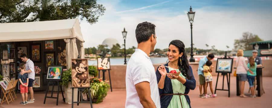 A man and woman smiling at one another while standing near outdoor art exhibits at Epcot