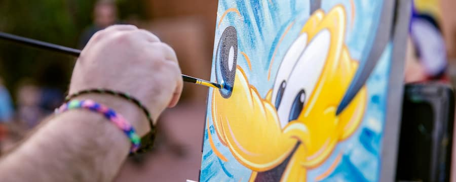An artist painting Pluto on a canvas