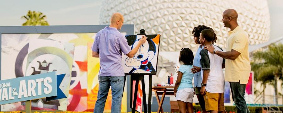 Uma família observa um artista colocar os toques finais em um retrato do Mickey Mouse no Epcot