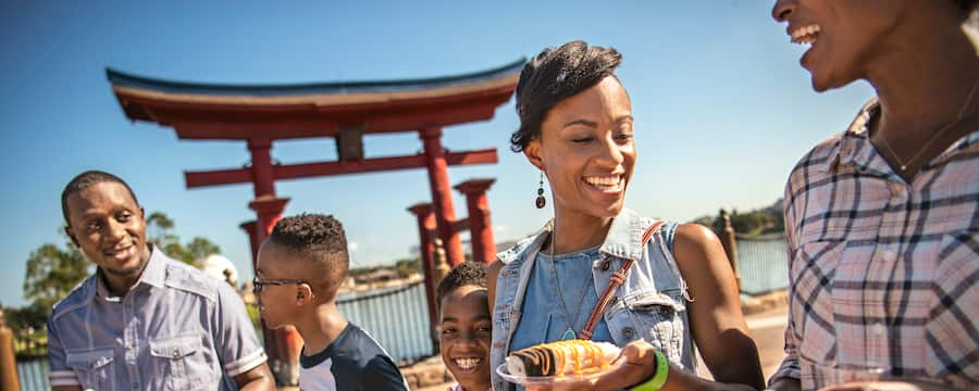 A family stands in a group at World Showcase smiling and holding plates of food