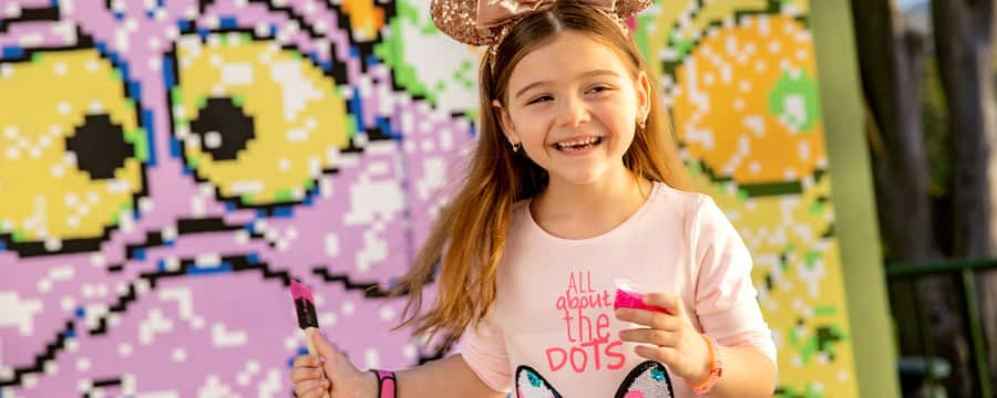 A girl wearing Minnie Mouse ears holds a small container of paint and a brush