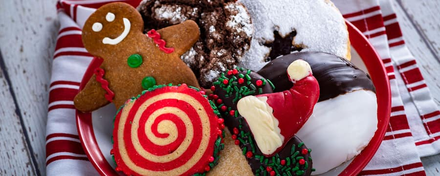 A plate filled with holiday themed cookies like a gingerbread man and a Mickey Mouse shaped cookie with a Santa hat