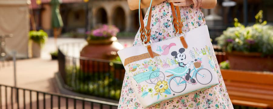 Lady stands in World Showcase with Minnie Mouse purse