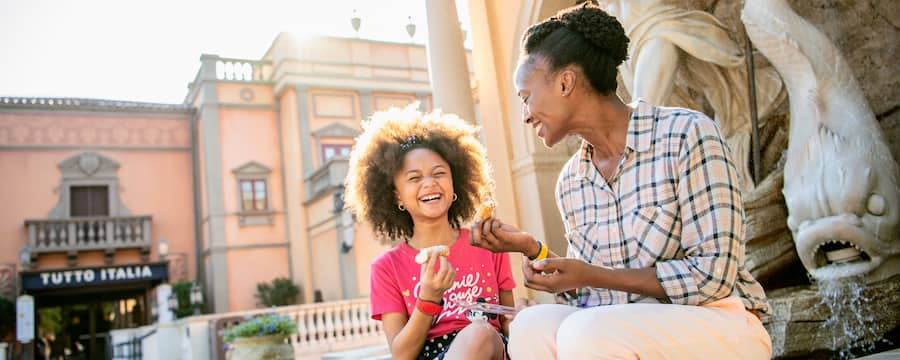 Mom and young daughter sit on fountain in Epcot Italy enjoying festival food