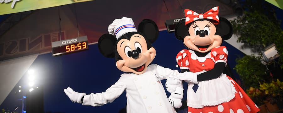 Mickey Mouse, dressed as a chef, stands with Minnie Mouse at the finish line for Disney Wine and Dine Half Marathon.