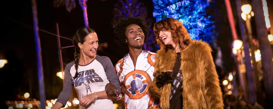 3 young adults laugh together while attending the Star Wars Galactic Spectacular