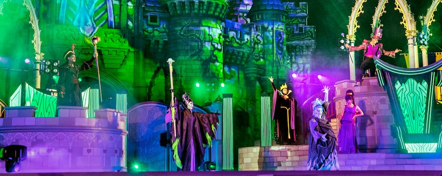 Maleficent, Hades, Meg, The Queen, Jafar and Doctor Facilier pose on stage in front of Cinderella Castle