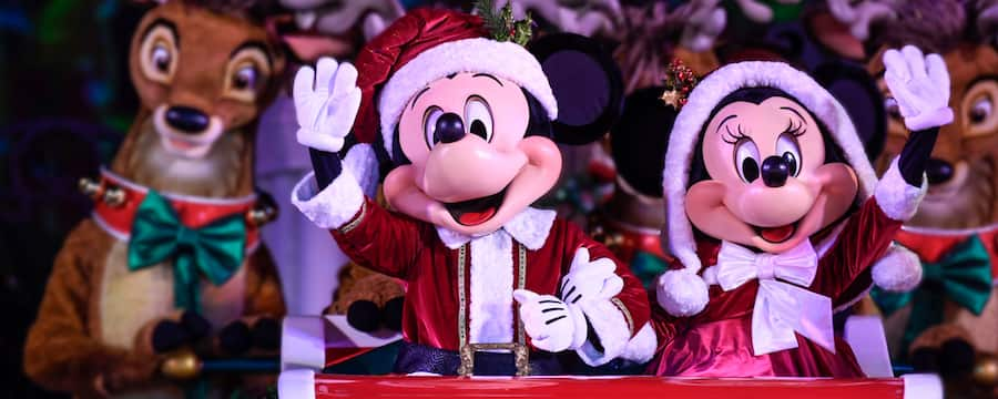 Mickey and Minnie, dressed like Santa and Mrs. Claus, ride in a sleigh surrounded by reindeer