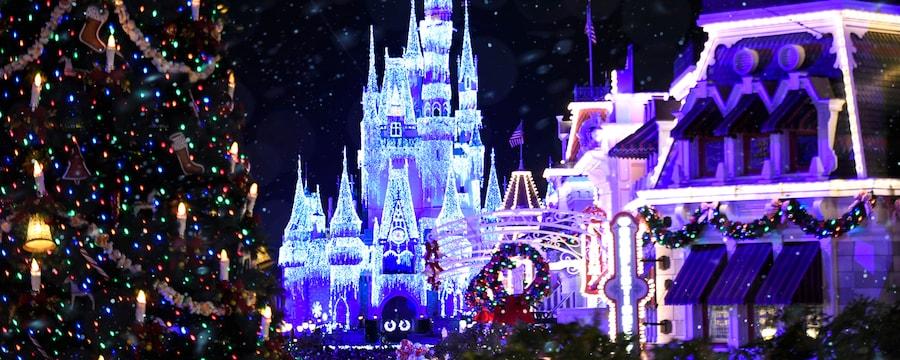 Un gran árbol de Navidad delante de Cinderella Castle con nieve cayendo sobre Main Street, U.S.A.