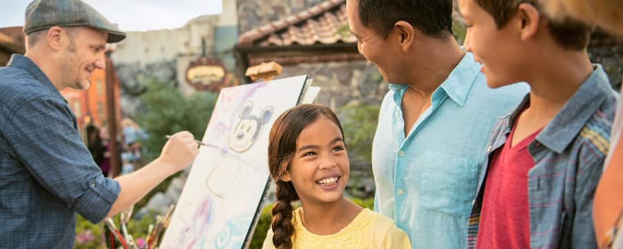 A little girl grins at her family as they watch artist David Buckley paint a Mickey Mouse picture