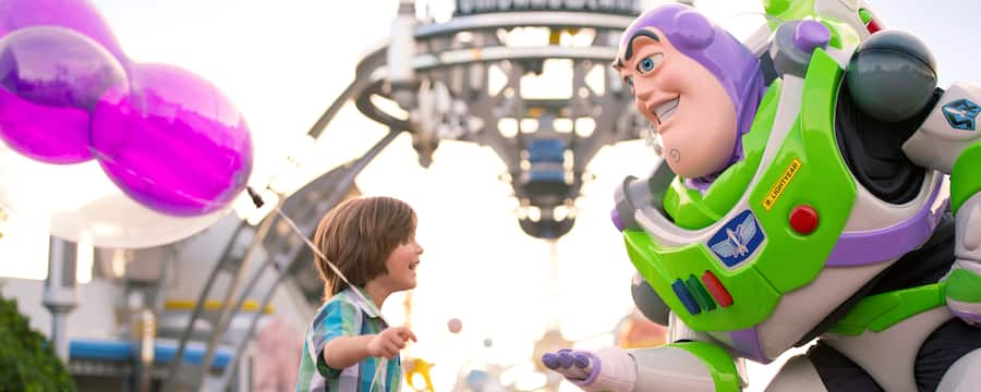 Buzz Lightyear from the Toy Story films stoops to talk to a little boy with a balloon
