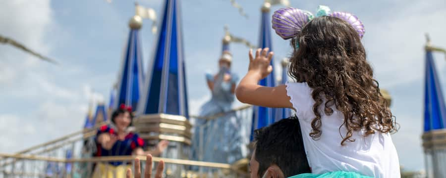 Little girl sits on her father's shoulder's as she waves to Snow White passing by on a float