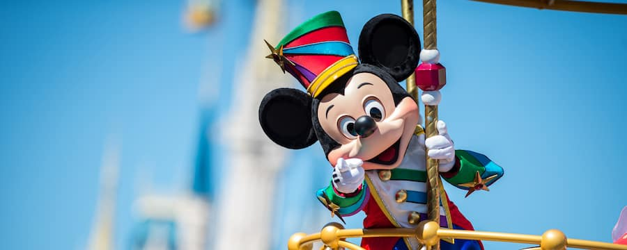 Mickey Mouse points while standing on a parade flaot in front of Cinderella Castle