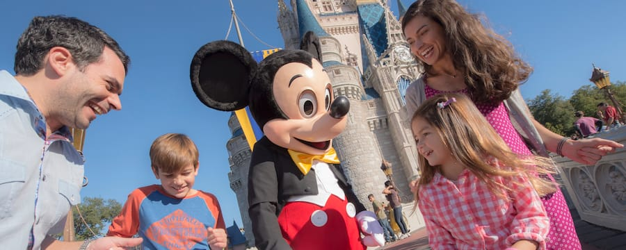 A family smiles with Mickey Mouse in front of Cinderella Castle