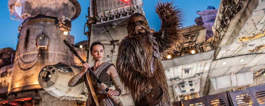 Rey holds her staff and Chewbacca waves in front of the Millennium Falcon