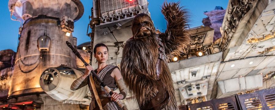 Rey segura seu bastão e Chewbacca acena em frente à Millennium Falcon