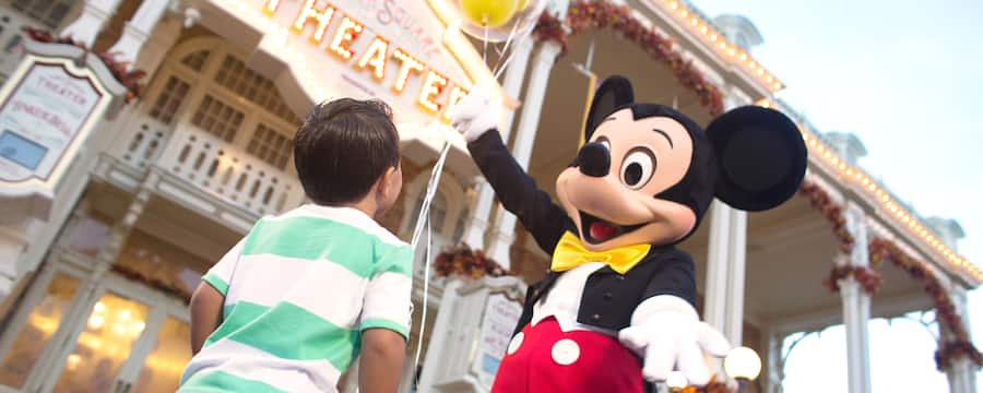 Mickey Mouse offers a bunch of balloons to a young Guest at Magic Kingdom park