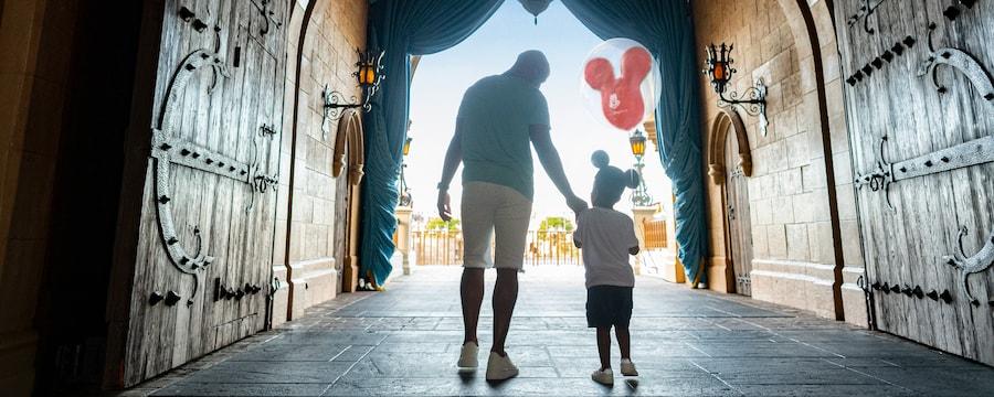 Dad and son walk through Cinderella's Castle holding a Mickey Balloon