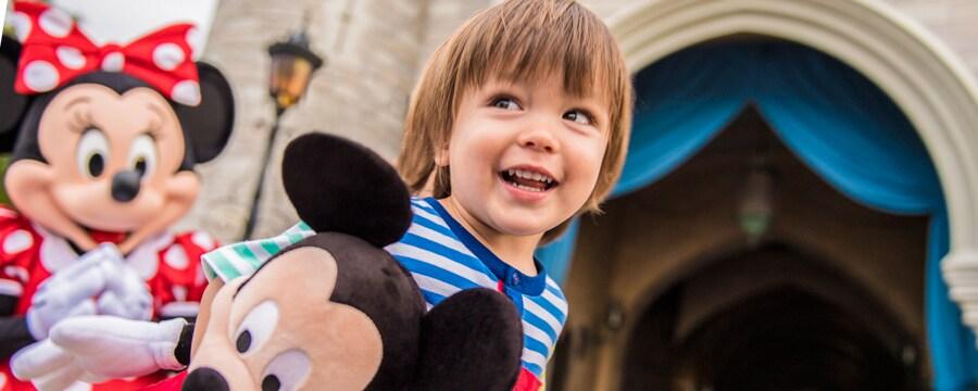 Minnie Mouse parada junto a un niño que sostiene un muñeco de Mickey Mouse