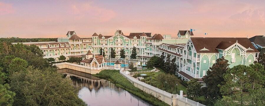 Un hotel victoriano inmenso frente a un lago apacible con hileras de árboles y vegetación
