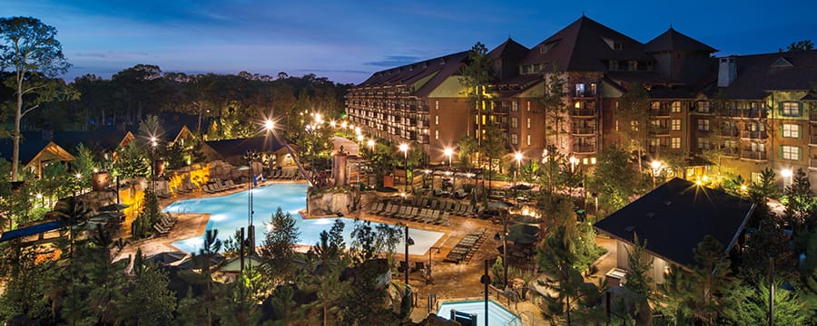 Alpine trees surrounding a multistory wood and stone wilderness lodge with an impressive pool area