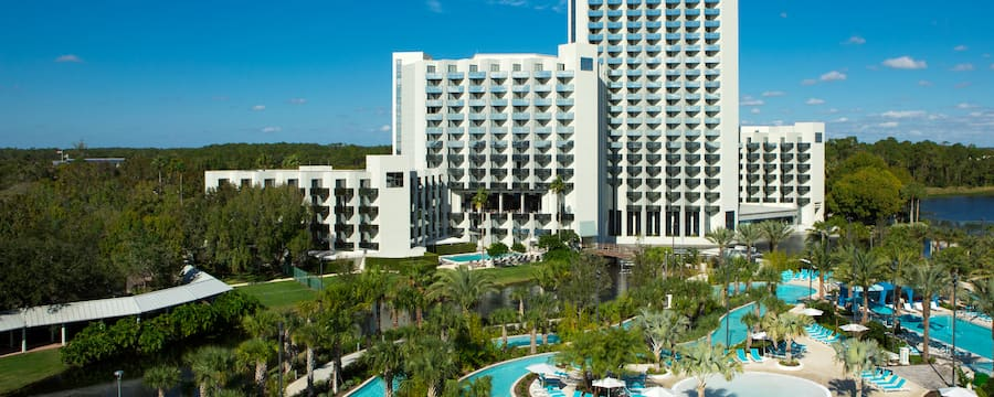 A large hotel featuring a winding pool lined with reclining beach chairs and palm trees