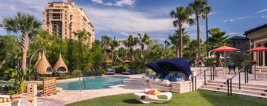 Área de la piscina de un hotel con muebles abstractos y sombrillas, y juegos como Jenga gigante y Connect4