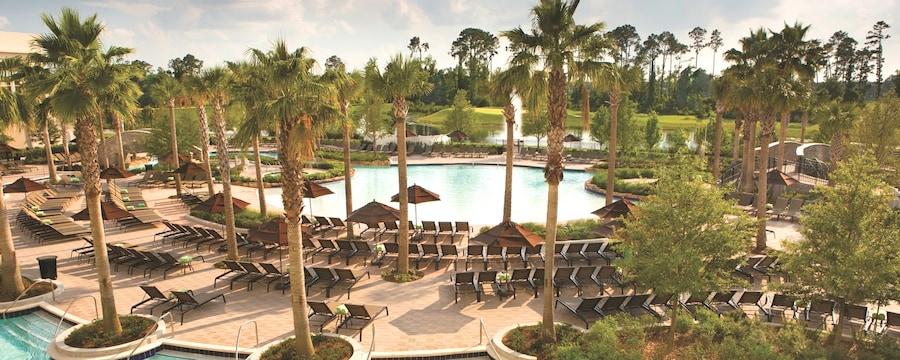 Uma área grande de piscina em um resort com cadeiras de praia, guarda-sóis e muitas palmeiras