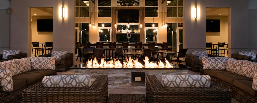 Rattan sectional sofas around a large firepit, with a bar in the background
