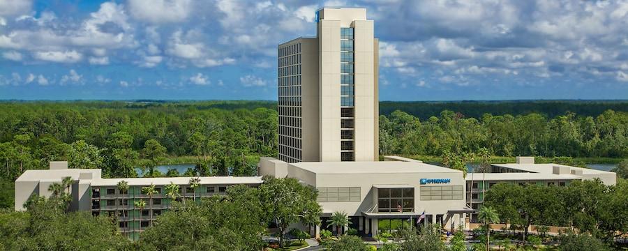 La torre de un hotel con muchas ventanas, detrás de copas de árboles circundantes