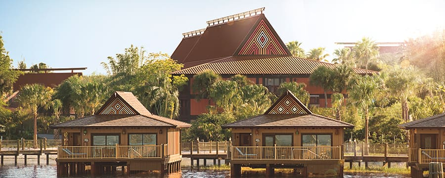 Three bungalows along the water with palm trees in the background