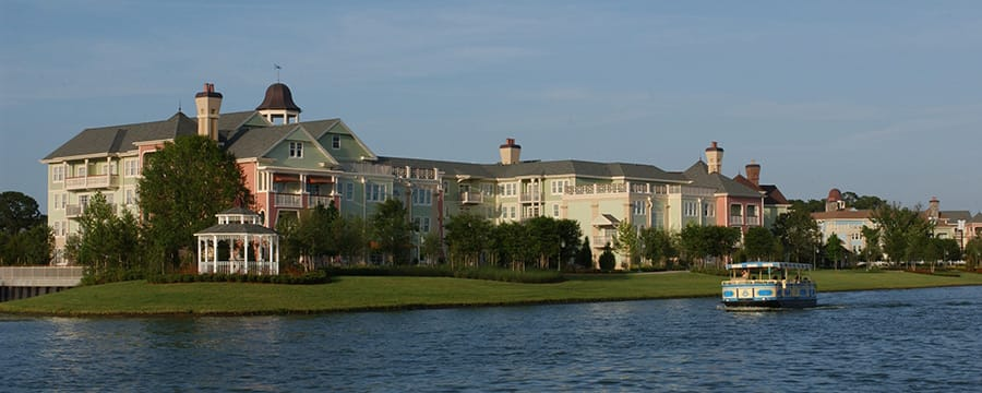 An open aired riverboat sailing alongside the Victorian style Disney's Saratoga Springs Resort and Spa