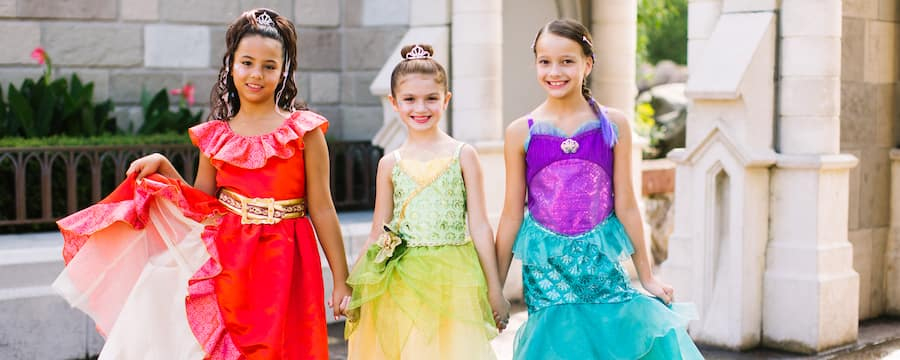 3 girls in princess dresses and fancy shoes pose in front of Cinderella Castle