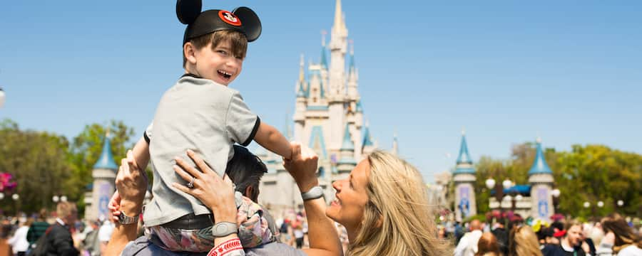 A boy wearing Mickey ears sits on top of his father's shoulders in front of Cinderella Castle