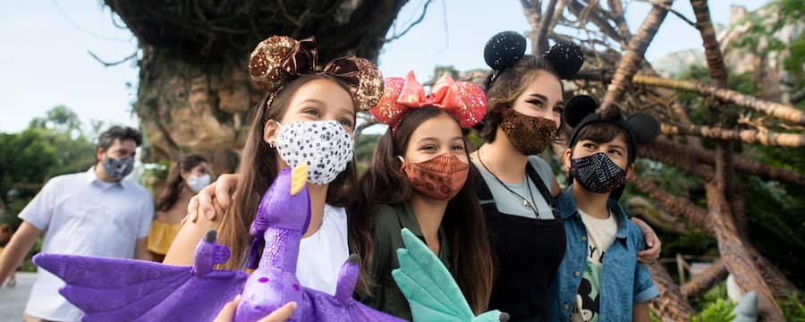 Family with facemasks walk together in Pandora World of Avatar with plush banshees.