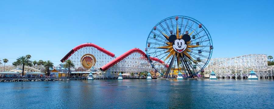 A view from the water of Pixar Pier that includes the Incredicoaster and the Pixar Pal A Round Ferris wheel.