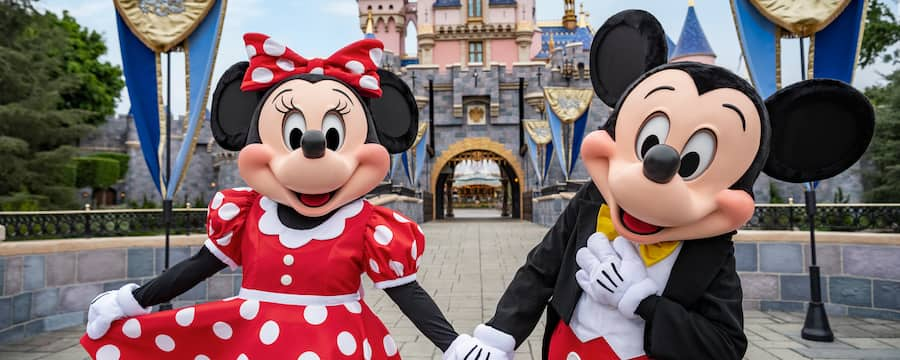 Mickey and Minnie Mouse hold hands while standing near the entrance to the Sleeping Beauty Castle walk through
