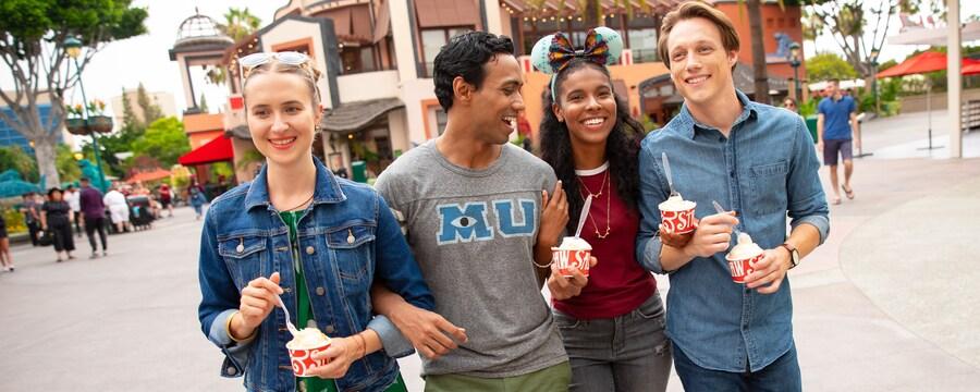 Cuatro Visitantes jóvenes reunidos comiendo bocadillos