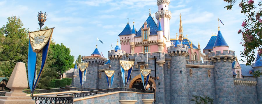 Surrounded by water, Sleeping Beauty Castle features a flag lined bridge leading up to its entrance