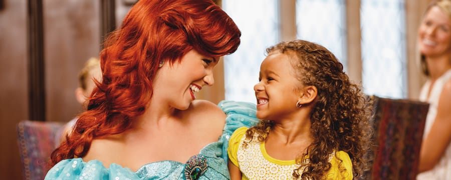 Princess Ariel shares a smile with a young Guest who is sitting in her lap