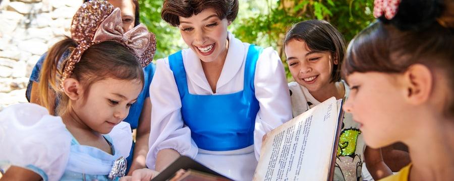La Princesa Disney, Belle, muestra las páginas de un libro a un grupo de niñas jóvenes.